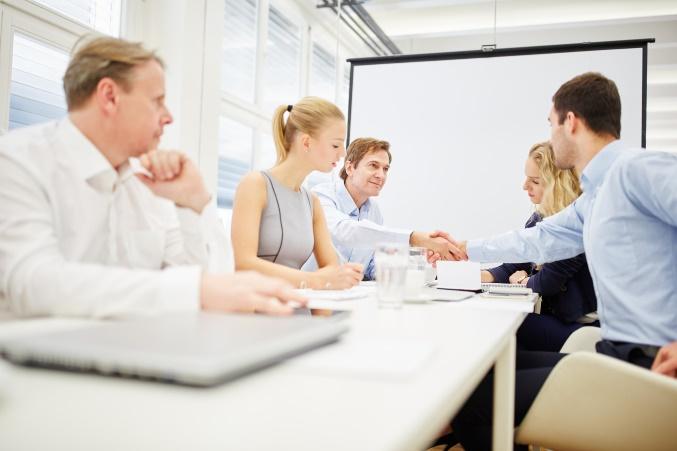 Business Team macht Handschlag beim Meeting im Konferenzraum